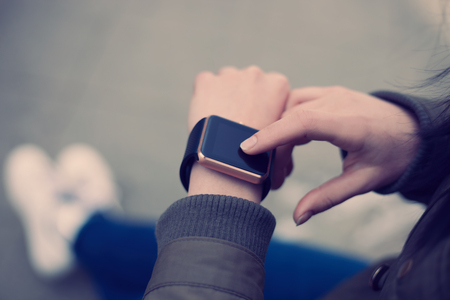 hands connected: Hands of a female using her trendy smart wrist watch. This new device lets you always stay connected to internet and social media networks from anywhere you want.