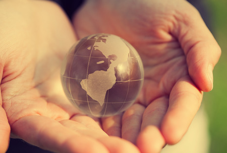 crystal glass: Macro photo of human holding a crystal glass globe model. Concept for peace, love and unity.