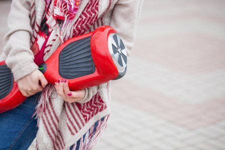 holding hands while walking: Female model holding modern red electric mini segway or hover board scooter in hands while walking in the park. Popular new transportation technology that produces no air pollution to the atmosphere. Girl is wearing trending boho style clothes. Stock Photo