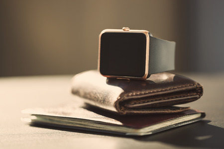 New smart watch lying on the wallet and passport. Thigns you carry with you every day when you go out of the house