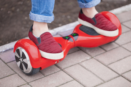 gir: Feet of a gir in marsala shoes riding on modern red electric mini segway or hover board scooter. Trending new transportation technology that is so much fun and easy to ride and produces no air pollution to the atmosphere. Focus on the device Stock Photo
