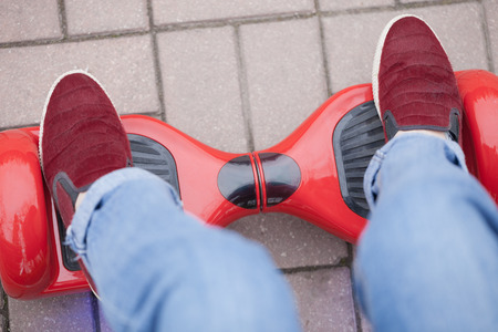 gir: Close up on feet of a gir in marsala shoes riding on a modern red electric mini segway or hover board scooter. Trending new transportation technology that is so much fun and easy to ride and produces no air pollution to the atmosphere.
