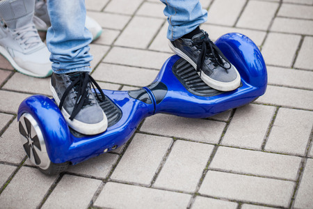 hover: Kid standing on a modern blue electric mini segway or hover board scooterin outdoors. Popular new city transport that is easy and fun to ride and makes no air pollution to the atmosphere