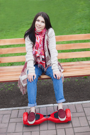 hover: Young white brunette woman holding modern red electric mini segway or hover board scooter in hands while sitting on a bench in a park. Popular new electric city transport. Girl is wearing trending boho style clothes.