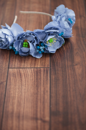 Handmade floral wraith made of blue flowers lying on the dark brown wooden background. Shallow depth of field, macro close up, copy space on the bottom