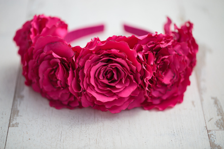wraith: Handmade wraith made of artificial red roses flowers on a white wooden background. Shallow depth of field, macro close up photo, no models, copy space on bottom