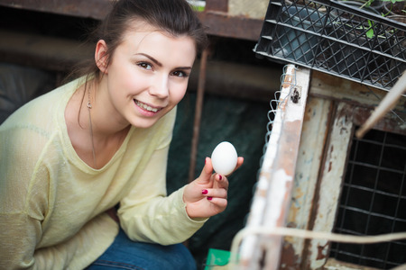 henhouse: Smiling young farmer girl holding a domestic chicken egg in her hand with henhouse on the background. This natural food ingredient is very important in farm household