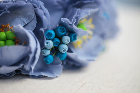 wraith: Handmade wraith made of artificial blue flowers lying on the bright white wooden background. Shallow depth of field, macro close up, no models