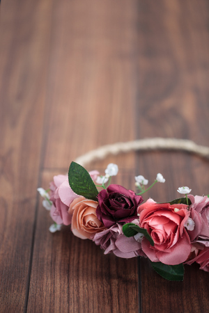 coronet: Handmade wraith or diadem made of pink and red rose flowers lying on the wooden surface. Shallow depth of field, macro close up, copy space on the bottom Stock Photo