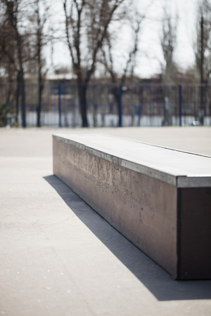 skate park: Ledge for doing tricks, grinding in outdoor skate park.