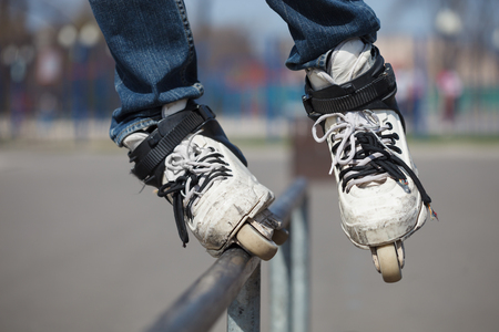 rollerskater: rollerskater grinding on rail in skate park outdoors.