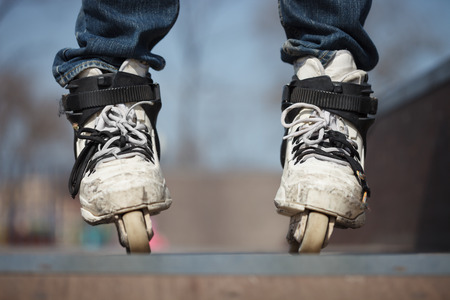 rollerblades: Rollerblader in skatepark wearing professional extreme inline rollerblades made for tricks - grinding and jumping. Dangerous sport popular among youth and teenagers.