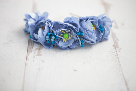 wraith: Handmade wraith made of artificial blue flowers lying on the bright white wooden background. Stock Photo