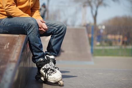 blader: rollerskater sitting in skatepark wearing professional extreme inline skates