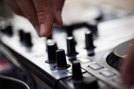 midi: Hands of male Dj playing music on modern midi controller turntable.