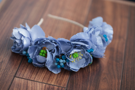 wraith: Handmade floral wraith made of blue flowers lying on the dark brown wooden background. Stock Photo