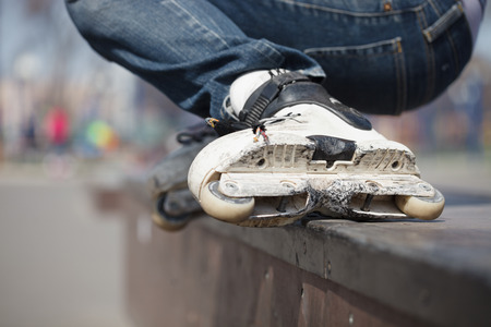 blader: Rollerblader grinding on rail in skate park outdoors.Trick is called backside royale. Dangerous extreme skating popular among youth and teenagers.