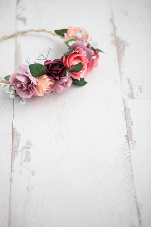 wraith: Handmade wraith or tiara made of pink and red rose flowers lying on bright white wooden background.