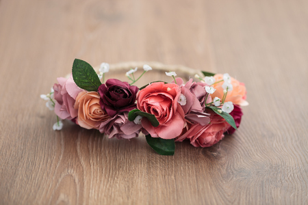 wraith: Handmade wraith or diadem made of pink and red rose flowers lying on the wooden surface.