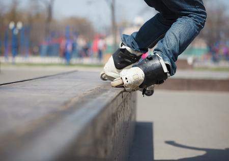 skate park: rollerskater grinding on rail in skate park outdoors.
