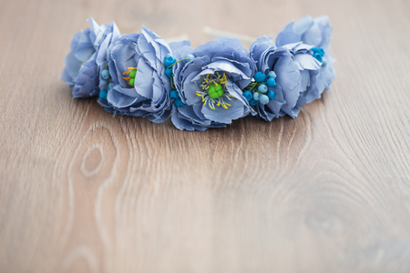 wraith: Handmade floral wraith made of blue flowers lying on the brown wooden background.