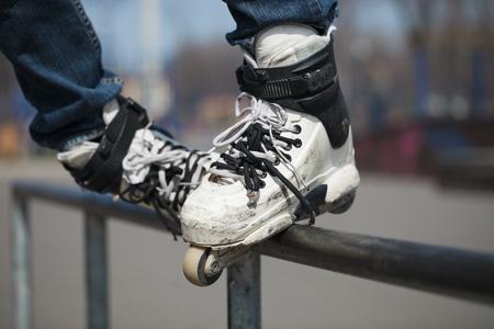 rollerskater: Rollerskater grinding on rail in skate park outdoors. Stock Photo