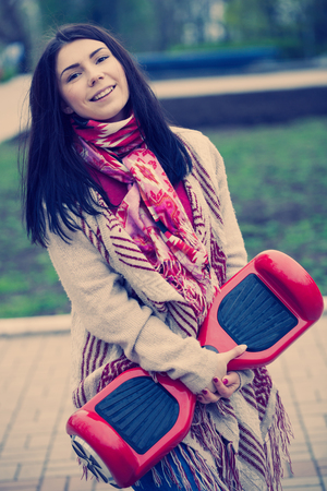 hover: Female model holding modern red electric mini hover board scooter in hands while walking in the park.