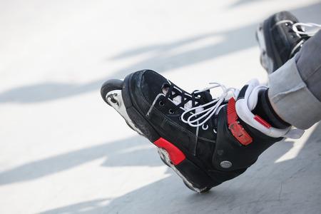blader: Feet of rollerskater wearing aggressive inline skates sitting on a concrete ramp in outdoor skate park.
