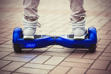 Person riding a modern blue electric mini or hover board scooter in outdoors.