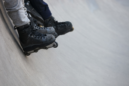 inline: Feet of rollerskater wearing aggressive inline skates sitting on a concrete ramp in outdoor skate park.