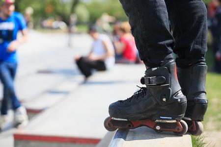blader: Feet of rollerskater wearing aggressive inline skates standing on top of concrete ramp in outdoor skate park.
