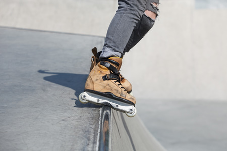 skate park: Feet of rollerskater wearing aggressive inline skates grinding on concrete ramp in outdoor skate park. Stock Photo