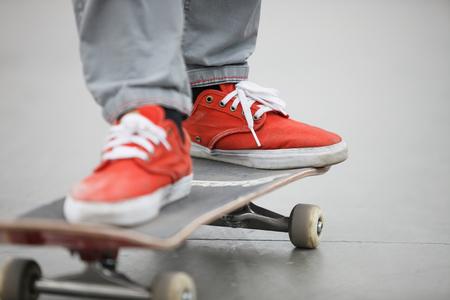 footwear: Skater riding a skateboard on concrete. Focus on orange footwear and skate board.