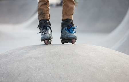 inline: Feet of aggressive inline skater standing on ramp ready to roll. Stock Photo
