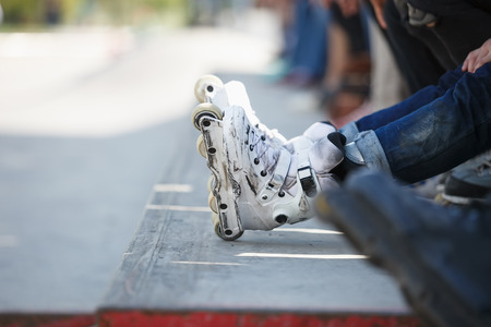 blading: Feet of rollerskater wearing aggressive inline skates sitting on a ledge with crowd in outdoor skate park.
