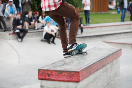 skate park: Skateboarder boy grinding on a ledge in outdoor skate park.