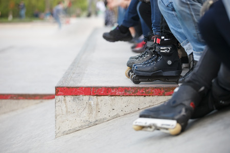 blader: Feet of guy wearing aggressive inline skates sitting on a ledge with crowd in outdoor skate park.