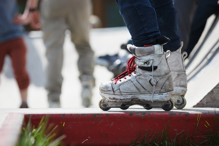 blading: Feet of man wearing aggressive inline skates standing on top of concrete ramp in outdoor skate park.