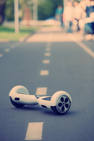 hover: White Electric mini hover board scooter on asphalt road.