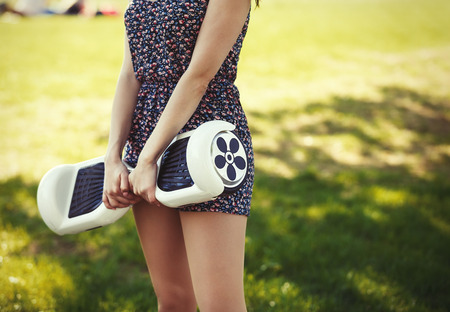 Female with electric mini hover board scooter in green park.