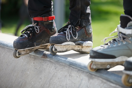 skate park: Feet of rollerskaters wearing aggressive inline skates standing on top of concrete ramp in outdoor skate park. Stock Photo