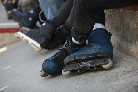 blader: Feet of roller skater wearing aggressive inline skates sitting on a ledge with crowd in outdoor skate park.