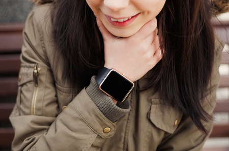 parka: Smiling young girl in parka coat wearing trendy smart watch. Stock Photo