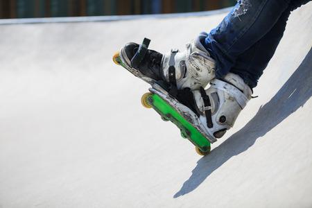 inline skater: Feet of roller skater wearing aggressive inline skates sitting on a concrete ramp in outdoor skate park.
