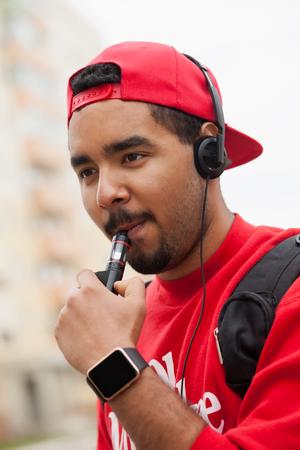 joven fumando: Retrato de hombre joven negro que usa el dispositivo vaporizador e-cig moderna para fumar tabaco líquido de glicerina con sabor. Foto de archivo