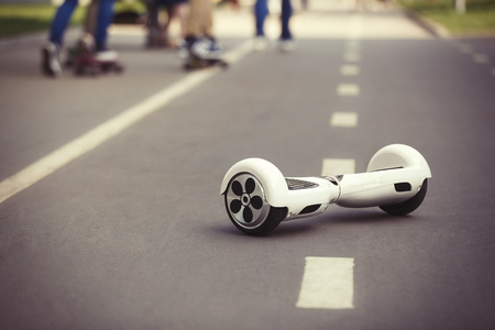 hover: White Electric mini hover board scooter on road in park. Stock Photo