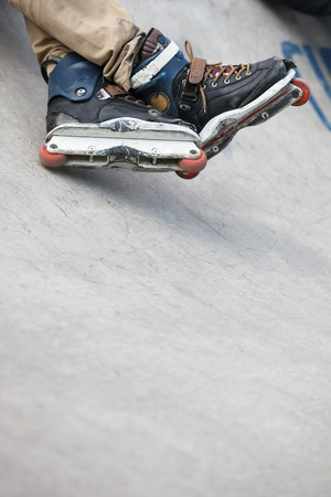 inline: Feet of roller skater wearing aggressive inline skates sitting on a concrete ramp in outdoor skate park.