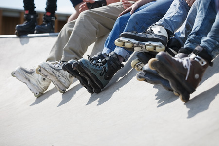 blading: Feet of rollerskaters team wearing aggressive inline skates sitting on a concrete ramp in outdoor skatepark.
