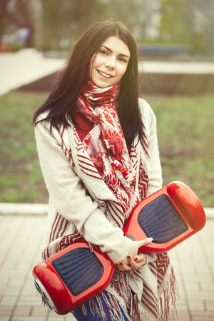 hover: Brunette white girl holding modern red electric mini hover board scooter in hands while walking in the park. Stock Photo