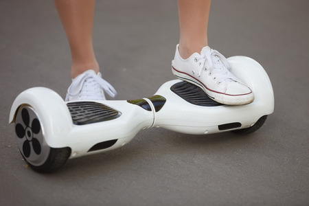 hover: Feet of girl riding electric mini hover board scooter outdoors in park.